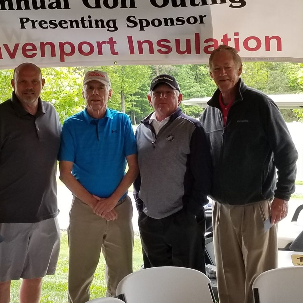 "men standing under banner that says ""Annual Golf Outing presenting sponsor Davenport Insulation"""